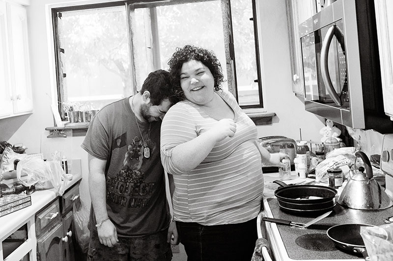brother and sister leaning on each other in kitchen