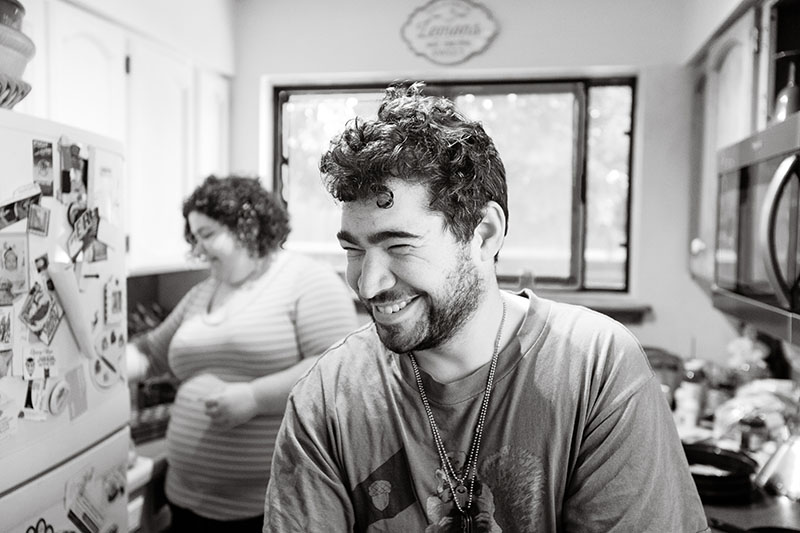young man laughing in kitchen