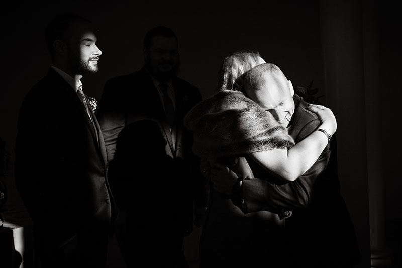 bridesmaid hugging groom black and white